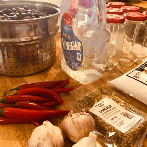 olives, garlic, vinegar and chilli on table