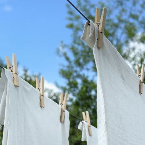 White laundry hanging outside from bamboo pegs