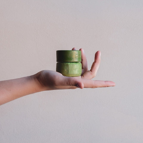 Hand with green shampoo bar and green conditioner bar