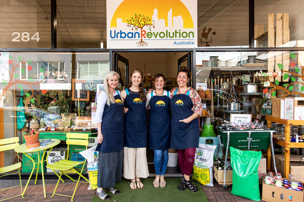 The Urban Revolution team smiling in their aprons and standing in front of the store entrance