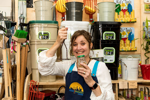 Jo from Urban Revolution holding a jar of Bokashi Composting Bran and a potato masher used with the Bokashi Kitchen Compost System