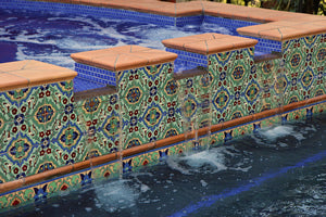 spanish tile design mixed with solid colored glazed porcelain tiles brings this pool to a