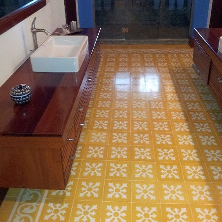A gracious master bath maintains a contemporary feel with floating vanities and a cement tile rug