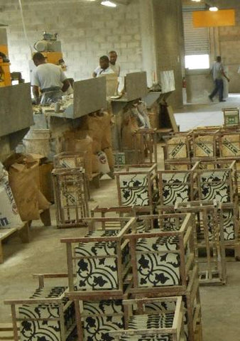 Cement tiles are placed on racks as they come off the line