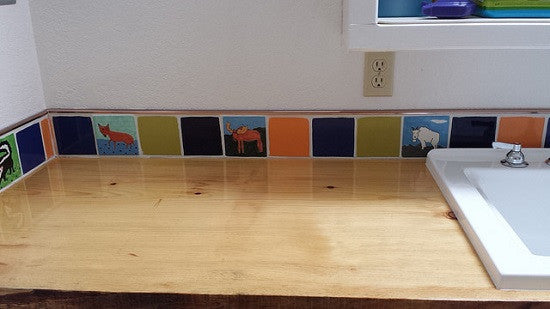 A collage of animal tiles and plain tiles makes for a fun addition to this laundry room