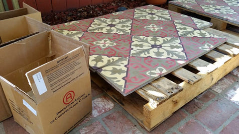 Cement tiles are removed from the box and placed on pallets prior to applying a grout release