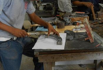 A cement tile mold is being worked on and checked against a pattern