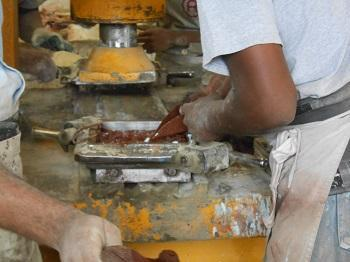 Colored cement being poured into the sections of a cement tile mold