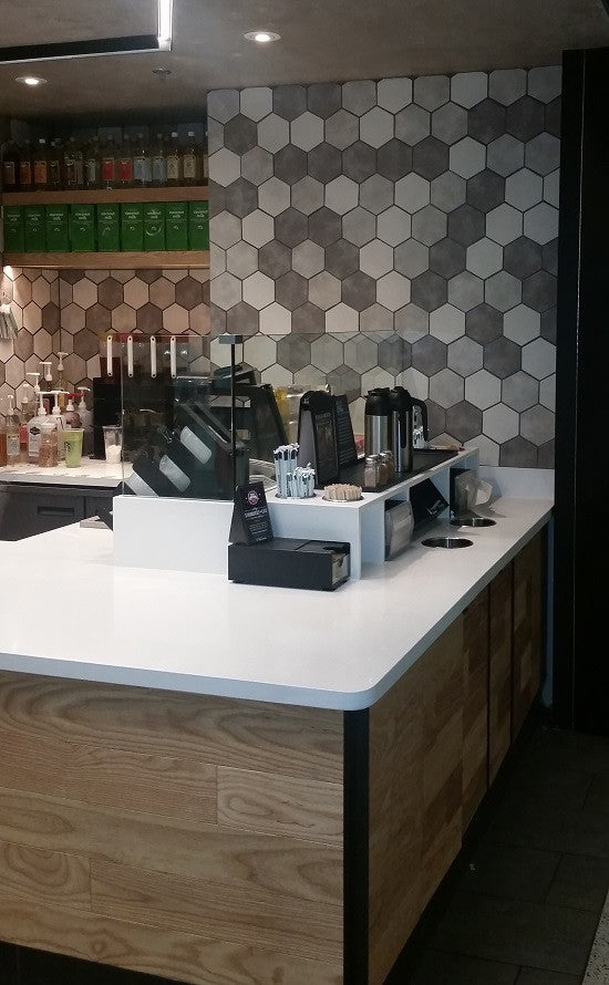 Glazed hexagon ceramic tiles in black, white and gray provide an eye-catching accent wall for this Starbucks