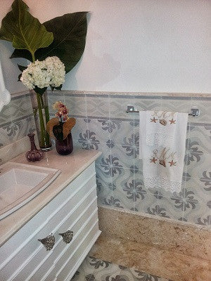 Cement tiles are used on the wall and floor in a powder room