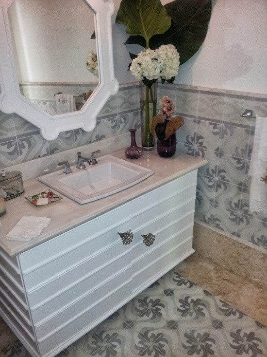 Soft colors mute a cement tile pattern in this powder room