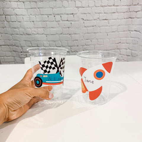 Clear plastic cups with race car sticker and rocket sticker