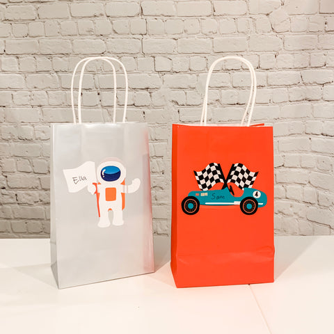 On left, Trip to the Moon Gift bag sticker on silver gift bag and on right, Vintage Race Car gift bag sticker on red gift bag