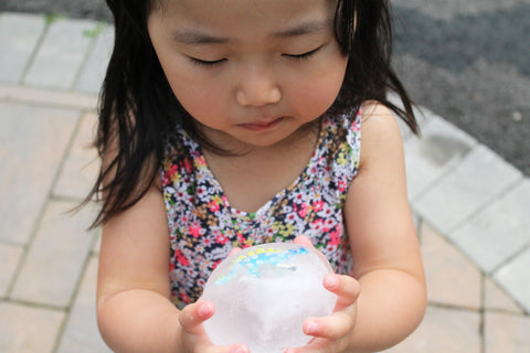 a girl holding a ice dinosaur egg