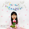 be my valentine banner with white swans with a girl holding a pink rose