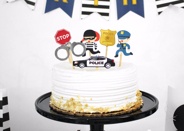 cops and robbers party cake and cupcake toppers featuring policeman, hand cuffs, badge, stop sign, and police car