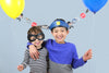 two children holding balloons and wearing a cop hat and a robber mask