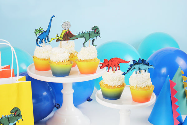 dinosaur cupcake toppers, dinosaur cupcake wrappers on cupcakes on white cake stands. Blue and teal balloons in the background
