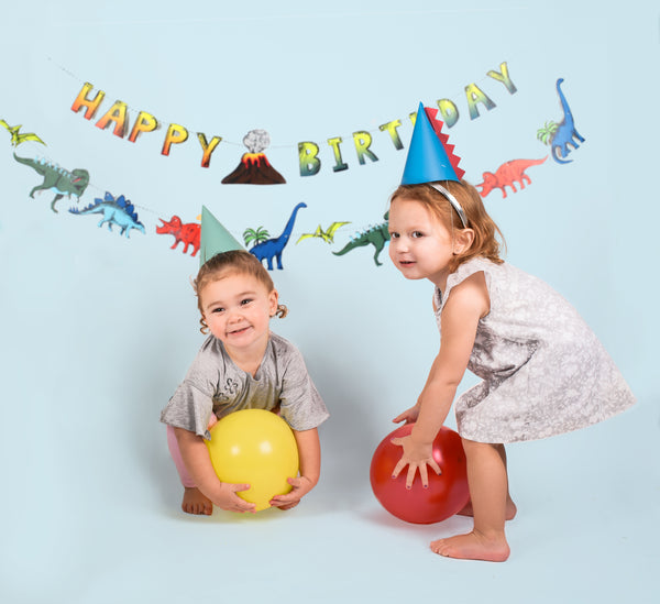 two children holding balloons and weraing dinosaur party hats