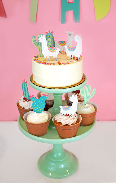llama and cactus cupcake toppers on a white cake and cupcakes