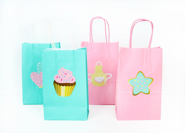 4 paper gift bags in teal and pink with cupcake and cookie stickers