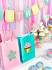 birthday party table with happy birthday banner, gift bags, cupcakes and cookies