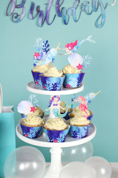 mermaid, narwhal, sea shell cupcake toppers on cupcakes wrapped with blue ocean print cupcake wrappers