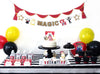 magic show party decorations with 'magic' banner, garland, cupcake toppers, red and gold gift bags and balloons.