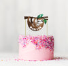 sloth cake topper on a pink cake with sprinkles