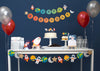 outer space party table with space birthday banner, garland, cupcake toppers, party hats, invitation, thank you cards and red and silver balloons