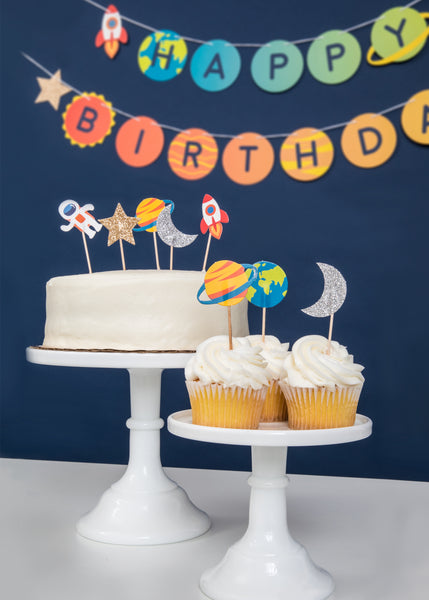 table scene with outer space themed cupcake toppers featuring astronaut, rocketship, planet, earth, star and moon