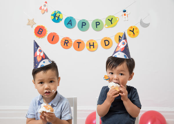 two boys eating cupcakes and wearing outer space themed party hats