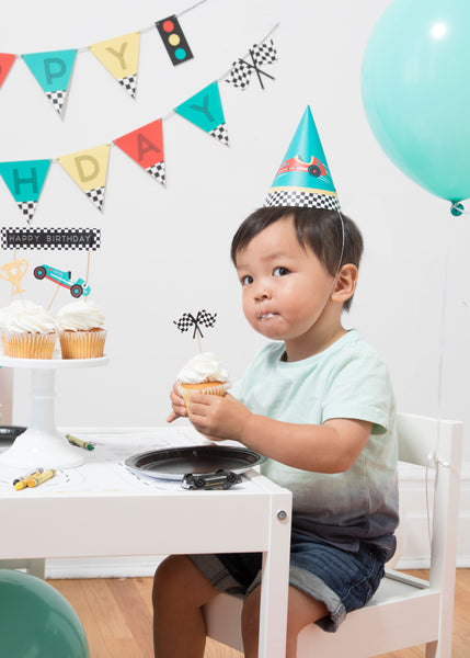a boy with a teal race car hat holding a cupcake with checkered flag cupcake topper