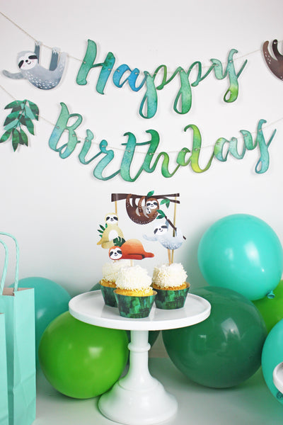 sloth cupcake toppers on cupcakes with white cupcake frostings on white cupcake stands. Happy birthday banner and green balloonsn in the background.