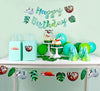 Complete table view of Sloth birthday party. There are sloth banner on the wall, sloth / tropical leaves garland hanging in front of table. On the bale, there's gift bags with sloth stickers, cupcakes with sloth cupcake toppers and wrappers, party hats and green/blue balloons