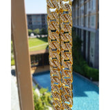 Stunning Gold N Diamond Cuban Link Chain hangs in an open window over looking a pool