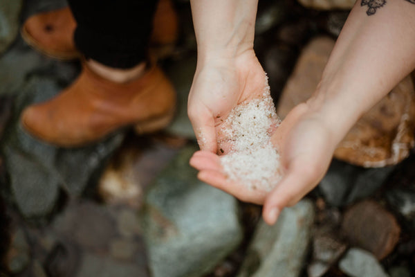 A pair of cupped hands hold a palmful of rainforest bath salts beside a natural creek bed