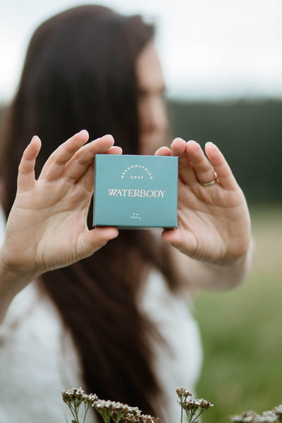 A woman standing in a meadow holds a bar of Meadowspring Soap with two hands