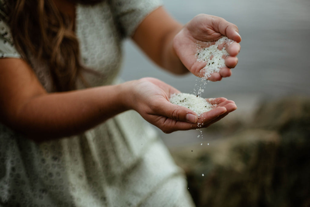 A woman sits beside the beach, pouring bath salts from one hand into another