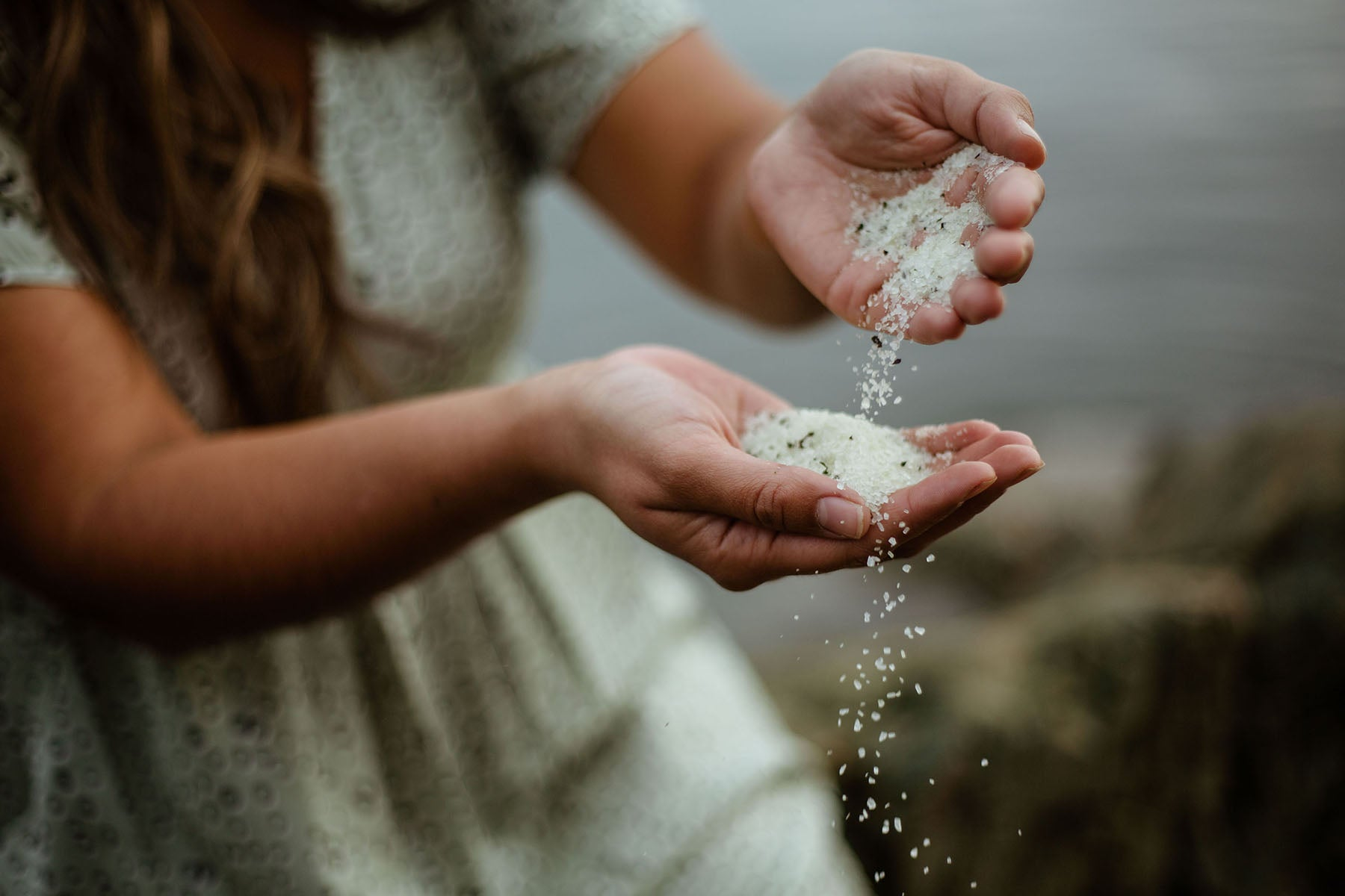 A woman sits beside the ocean and pours a sea salt bath soak from one palm into another