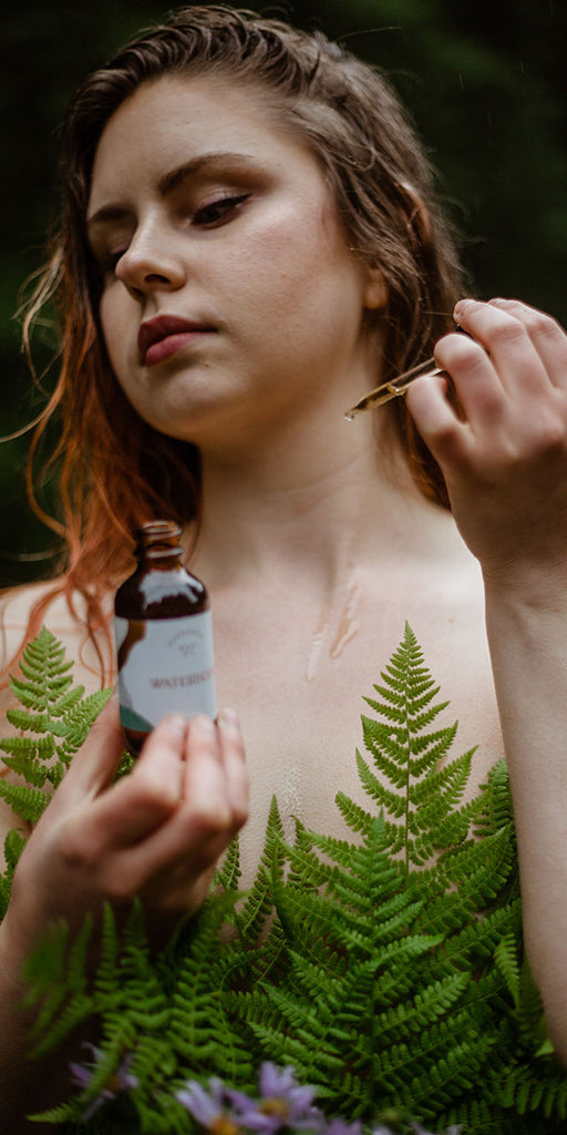A beautiful woman surrounded by lush ferns applies evergreen body oil to her skin