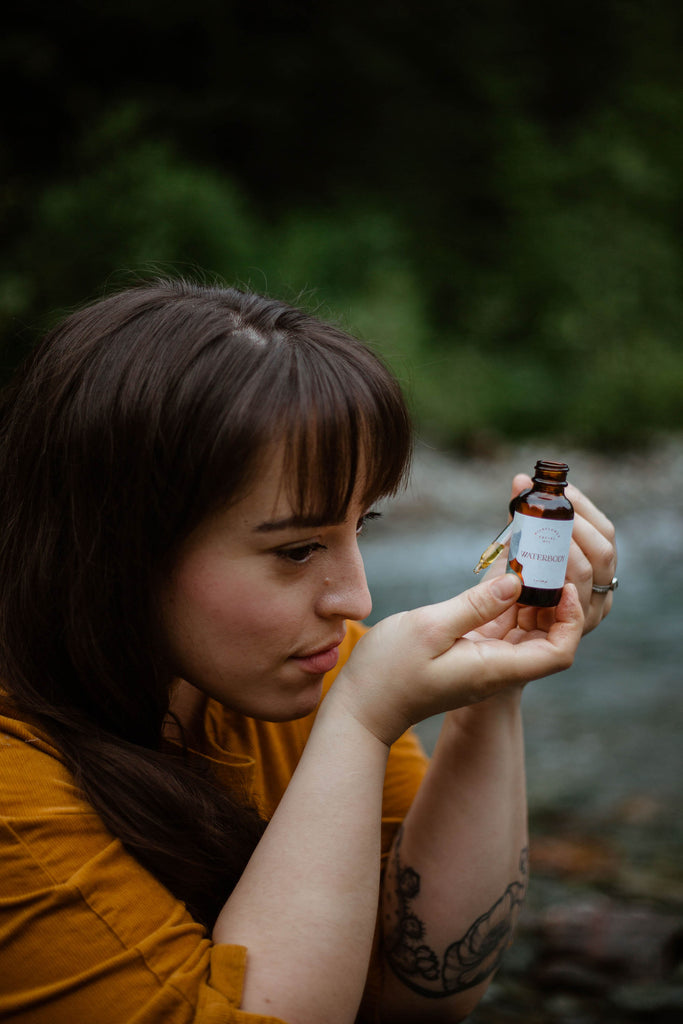 A woman enjoys the scent of wildflower facial oil beside a serene creek