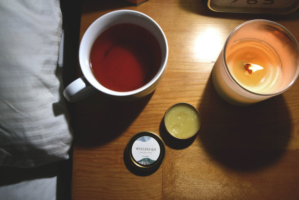 A cozy bedside table holds a flickering candle, warm cup of tea, and an open tin of Calm Body Balm
