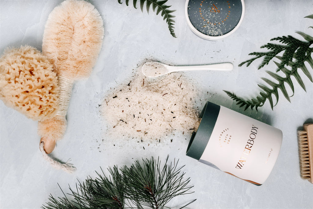 A tube of rainforest bath soak spills out, surrounded by a dry body brush, sea wool sponge, and green ferns and pine boughs