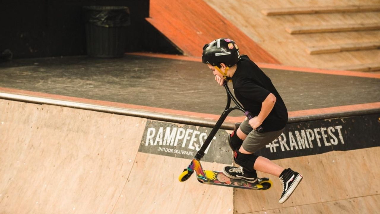Beginner Scooter Rider jumping the hip at RampFest Indoor Skate Park in Melbourne
