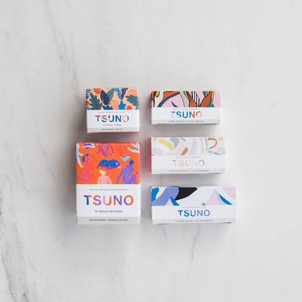 Image of 5 Tsuno products on a marble background.  Bamboo panty liners, bamboo regular pads, mini, regular and super organic cotton tampons.