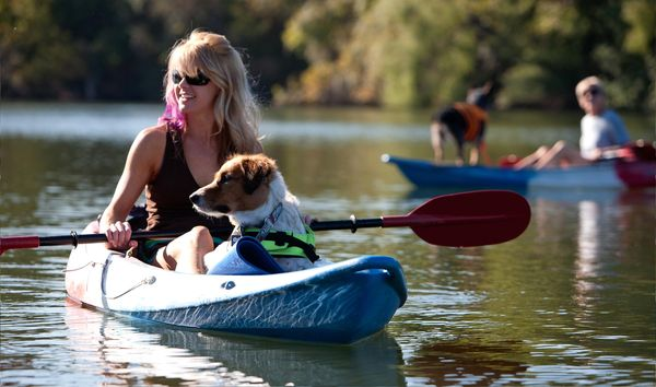 Lady and dog kayaking on lake