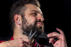 close-up of young man trimming his beard with comb and scissors