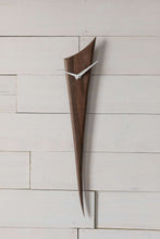 "Black Walnut Stake Clock is made of one solid piece of rich Black Walnut. This clock is understated, yet demands attention simply because of the gorgeous wood. Pointed white metal hands create a nice contrast with the wood. At 29"" high and 5.5"" wide, it is an ideal piece for small spaces. Stake Clock is simple and elegant with just a bit of whimsy."