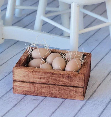 Dollhouse miniature eggs in wooden crate and straw